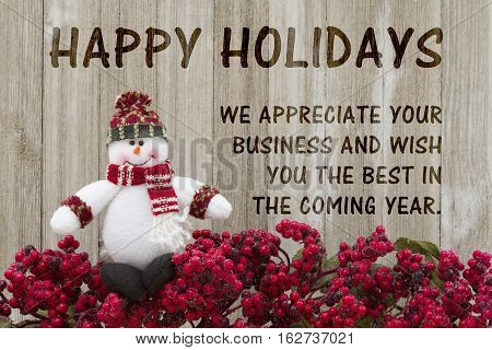 Old fashion Christmas greeting Frost covered red holly berries with a snowman on weathered wood background with text Happy Holidays and appreciating business