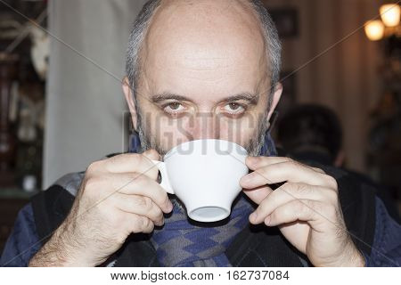 A middle-aged bald man drinking from a white cup at cafe