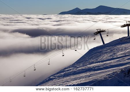 Winter mountains and ski lifts on a cloudy day.