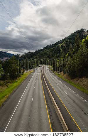 Interstate highway with dotted lines in lush, mountainous area. Cloudy skies above. Vertical orientation.