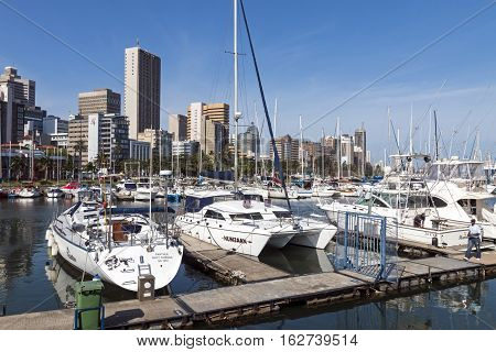 Vessels Moored At Yacht Mole Against City Skyline