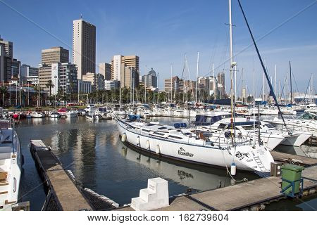 DURBAN SOUTH AFRICA - DECEMBER 19 2016: Vessels moored at yacht mole against city skyline in Durban South Africa