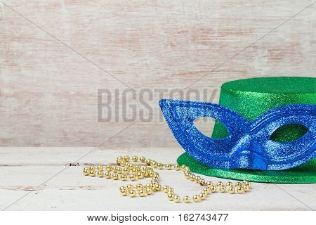 Mardi gras mask and hat for party on wooden background