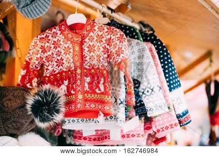 Various Colorful Knitted Traditional European Warm Clothes Sweaters At Winter Christmas Market. Souvenir From Europe.