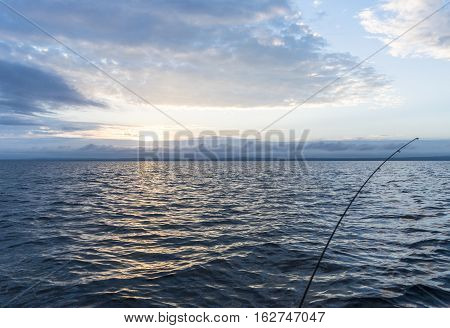 fisherman's spinning rod in the sun set