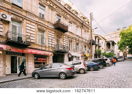 Tbilisi, Georgia - May 20, 2016: The View Of Narrow Paved Uphill Street With Old Architecture And A Row Of Parked Cars Along The Pavement In Summer Day Under Gray Somber Sky.