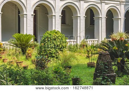 Patio with tropical plants in pots in the famous landmark - Basilica of Bom Jesus or Borea Jezuchi Bajilika. Basilica - UNESCO World Heritage Site and functioning church.