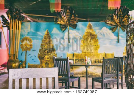 Wooden chair with traditional cafe interior background. The perfect place to taste Cambodian cuisine