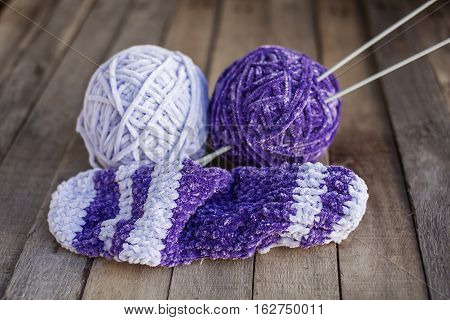Knitting: two balls of beautiful violet yarn with needles on wooden background. Hobbies. Selective focus.