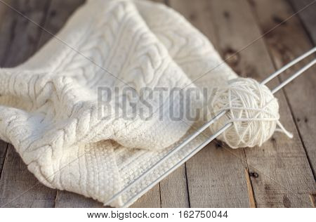 Beautiful knitted white scarf and ball of wool with needles on wooden background. Selective focus. Hobbies.