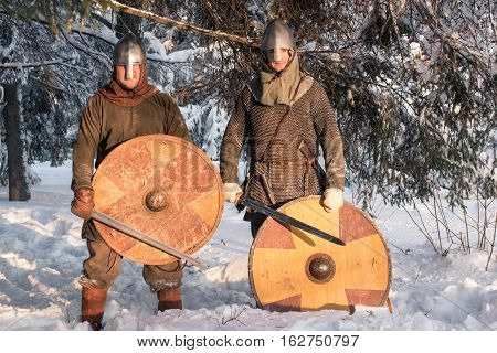 Two warriors in historical armor in winter forest