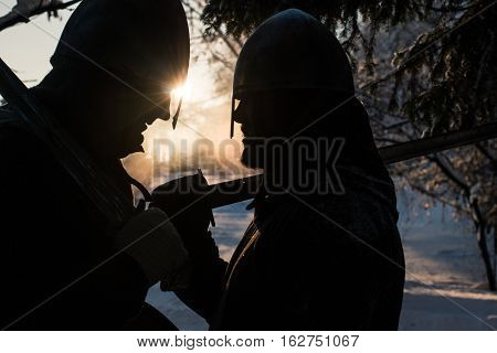 Silhouettes of two medieval warriors in winter forest