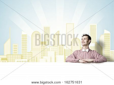 Young funny guy in checked shirt behind blank white banner