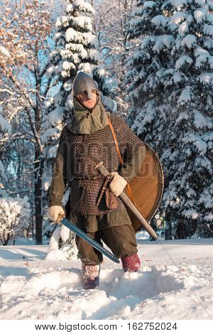 Warrior with sword in winter forest in armor
