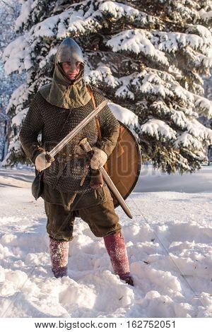 Swordsman standing in winter forest in armor