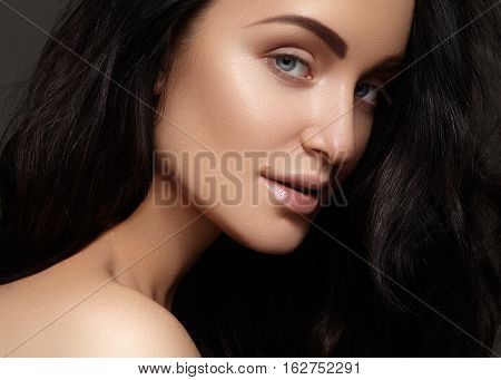 Beautiful young woman with volume curly hairstyle. Beauty portrait of brunette model with clean skin glow glamour fashion makeup. Make up hairstyle. Haircare make-up. Beauty portrait