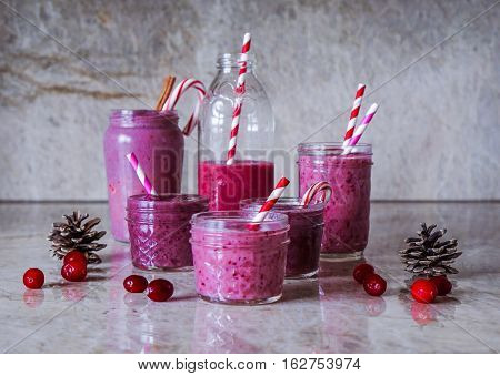 Juicy berry smoothies in glass, jars, bottles on marble background. Christmas cranberry theme. Selective focus. Toning.