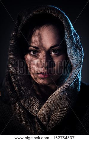 Scared young woman covering face with afghan scarf.