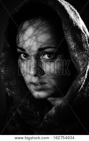 Beautiful frightened woman wrapped in a scarf on a black background. Monochrome photo, art noise.