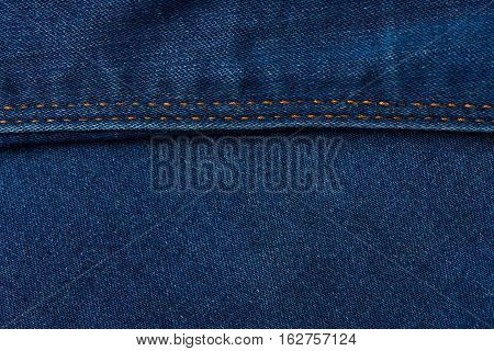 horizontal stiches on dark blue jeans background . Texture of blue jeans