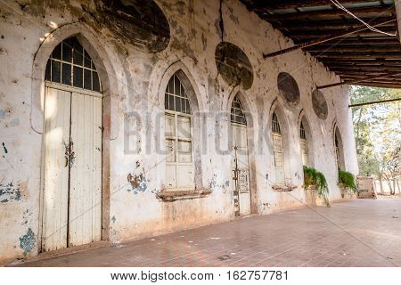 Horizontal photo in color, perspective and shallow depth of field, about an old white hacienda facade