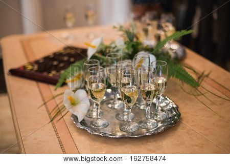 glasses of champagne on the table, wedding table piled with food, banquet, table setting