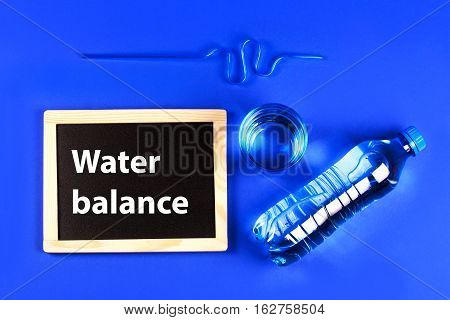 Glass, tube, closed bottle of water and chalkboard for text lying on blue background. Concept of freshness and observance of the water balance of human body.