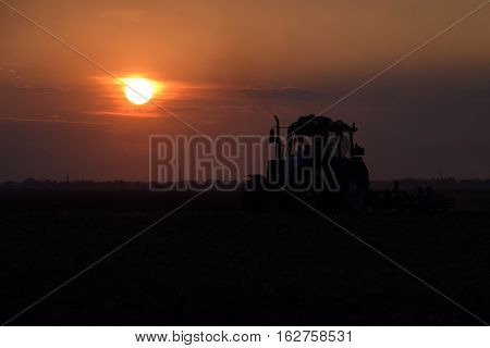Tractor Plowing Plow The Field On A Background Sunset. Tractor Silhouette On Sunset Background