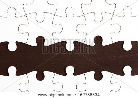 Incomplete puzzle on dark wooden table. Business and teamwork concept.