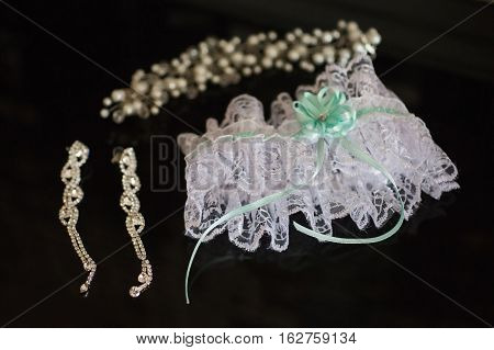 Garter of the bride women's earrings and bracelet lie on a white background wedding decorations fees bride preparing for the wedding wedding jewelry