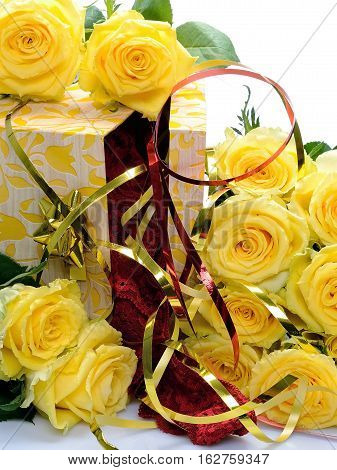 Ajar gift box with yellow flowers is surrounded roses on a white background