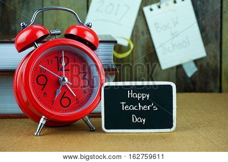 Happy Teacher's Day inscription written on chalkboard, red alarm clock, book on desk. Notes and old wooden background. Time concept.