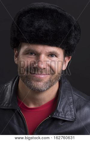 Portrait head shot of handsome smiling man wearing traditional Russian Ushanka hat and leather jacket