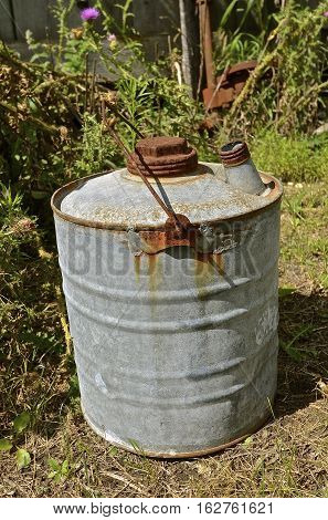 An old rusty five gallon gas and oil can used for transporting gas and oil.