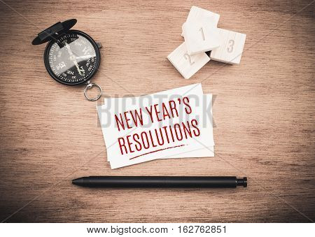 Top View Of  New Year's Resolutions Word On Business Card With Black Pen And Compass On Wooden Table