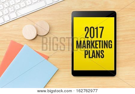Top View Of 2017 Marketing Plans On Screen Tablet With Blue Notebook And Keyboard On Wooden Beige Co