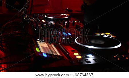 mixing table with red ligths in nigth club