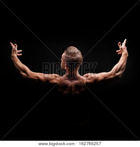 Bodybuilder posing on a black background. Dramatic portrait of an athlete. Drying. Relief and sculptural muscles of the body. Healthy lifestyle concept. The muscles of the shoulders.
