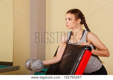 Cute girl doing exercise for biceps with hand weights. Working with free weight. Healthy lifestyle concept. Fitness.