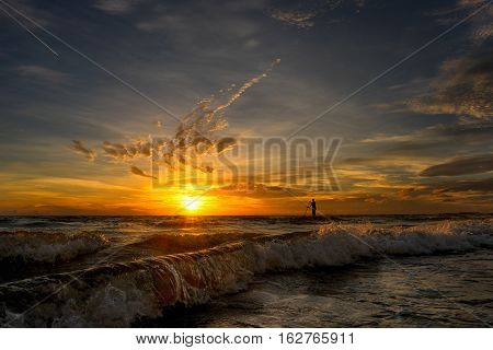 Paddleboarder in ocean at Sunset in Florida