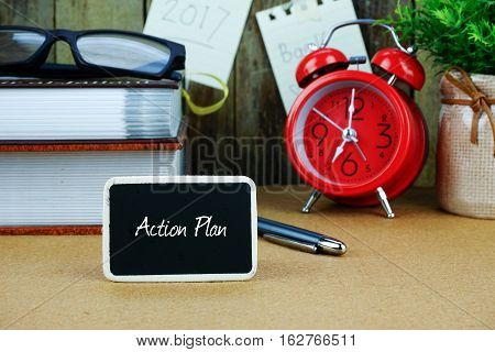 Action plan inscription written on chalkboard. Red alarm clock, book, spectacle, notes at background.