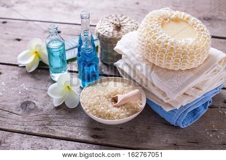 Spa or wellness setting in blue yellow and white colors. Bottles wih essential aroma oil wisp towels sea salt on aged wooden background. Selective focus.