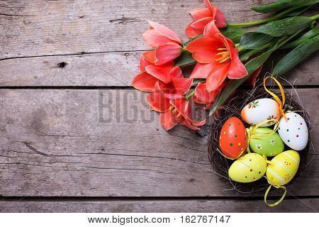 Easter background. Fresh tulips flowers decorative eggs in nest on vintage wooden background. Selective focus. Place for text.