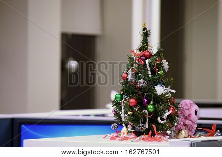 Cute miniature Christmas tree decoration in office cubicle image after hours in closed office workplace engaged employee decorated work environment with copy spce to list holiday office hours