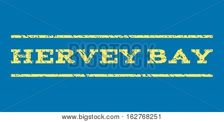 Hervey Bay watermark stamp. Text tag between horizontal parallel lines with grunge design style. Rubber seal stamp with unclean texture. Vector yellow color ink imprint on a blue background.