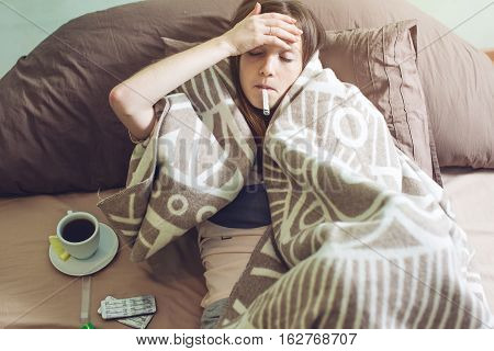Young Woman Sick With A Cold Lying In Bed