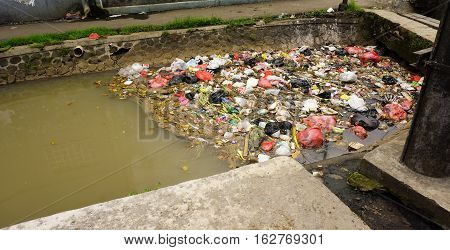 Trash clogs a dirty river photo taken in Bogor Indonesia java
