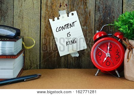 Content is king text written on sticky note. Book, pen, spectacle and red clock on brown desk. Education and business concept.