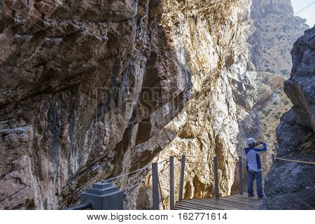 One trekker man walking along the Caminito del Rey path Malaga Spain. He is taking pictures with mobile phone