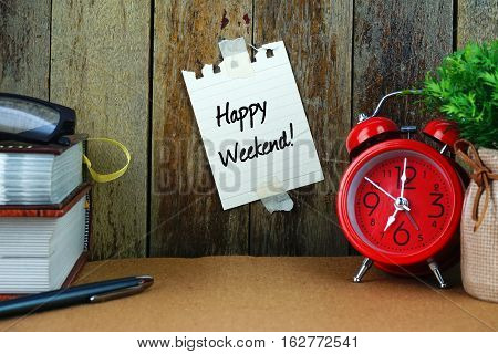 HAPPY WEEKEND! text written on sticky note. Book, pen, spectacle and red clock on brown desk. Education and business concept.